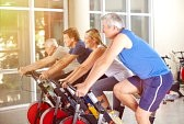 32598106-happy-group-in-gym-exercising-on-spinning-bikes-in-summer